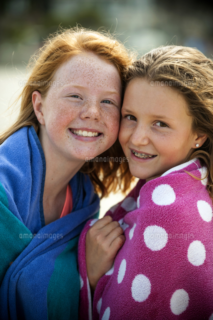 Portrait of smiling sisters wrapped in towels