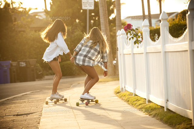 Teenage girls skateboarding on sidewalk