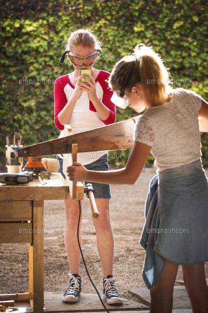 Girl photographing sister sawing wood in garage