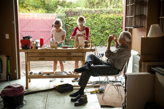 Grandfather photographing granddaughters building birdhouse in garage