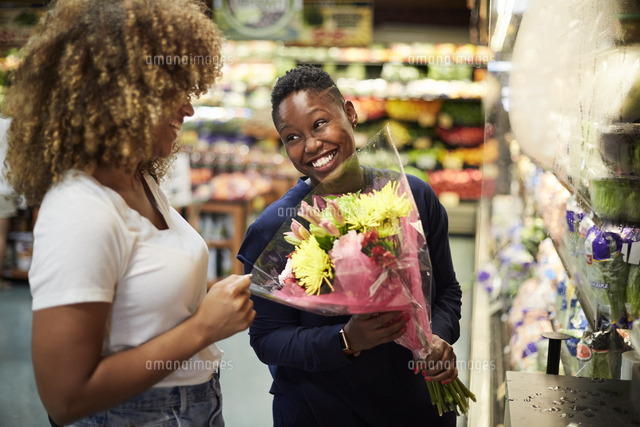 Black woman showing bouquet to girlfriend in store