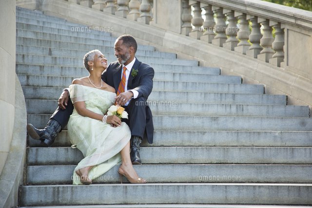 Black couple sitting on stone staircase