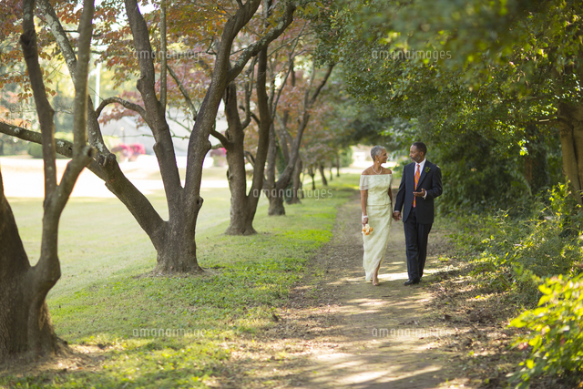 Black couple walking on path in park