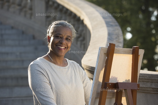 Black woman painting on canvas near stone staircase