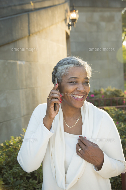Black woman talking on cell phone near stone staircase
