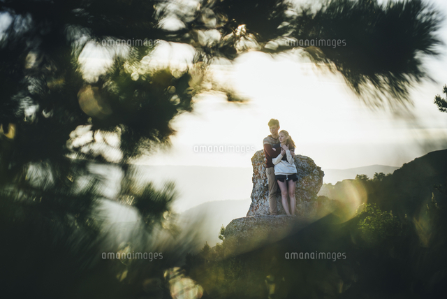 Tree branches framing Caucasian couple hugging at rock
