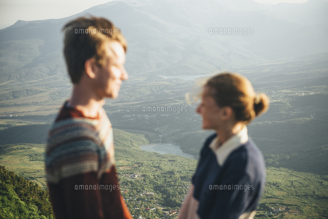 Caucasian couple standing on mountain over valley