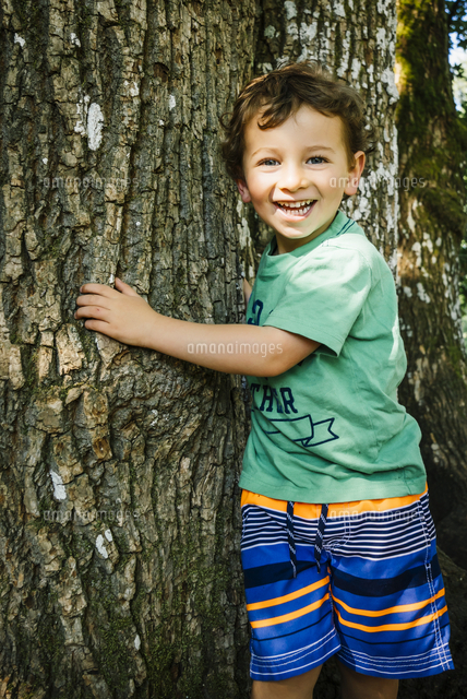 Portrait of smiling Caucasian boy hugging tree