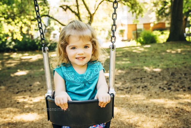 Caucasian preschool girl sitting in swing