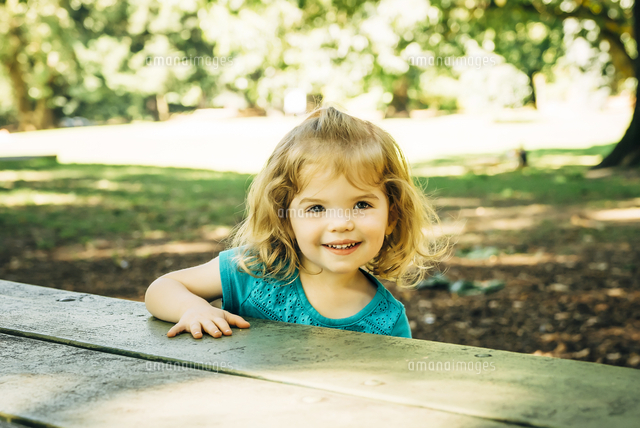 Portrait of Caucasian preschool girl at picnic table