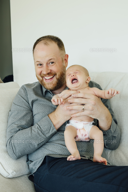 Portrait of smiling father holding crying baby daughter