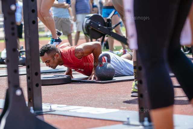 Man doing push-ups near kettlebell outdoors
