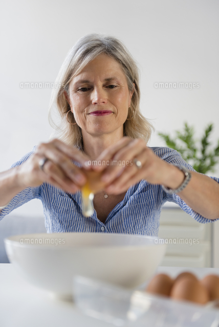 Caucasian woman cracking egg into bowl