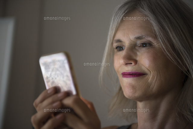 Smiling Caucasian woman texting on cell phone