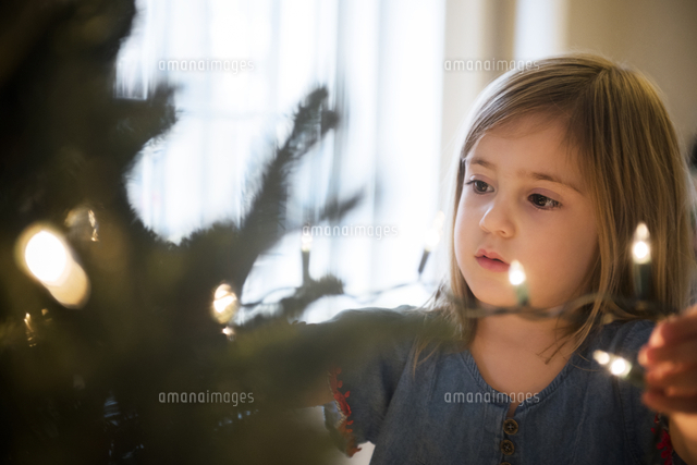 Caucasian girl hanging lights on Christmas tree