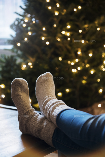 Socks of Caucasian woman with feet on table near Christmas tree