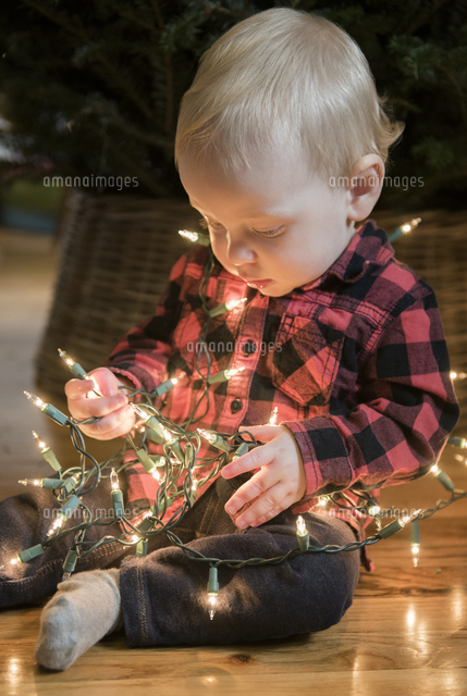 Caucasian baby boy sitting on floor wrapped in string lights