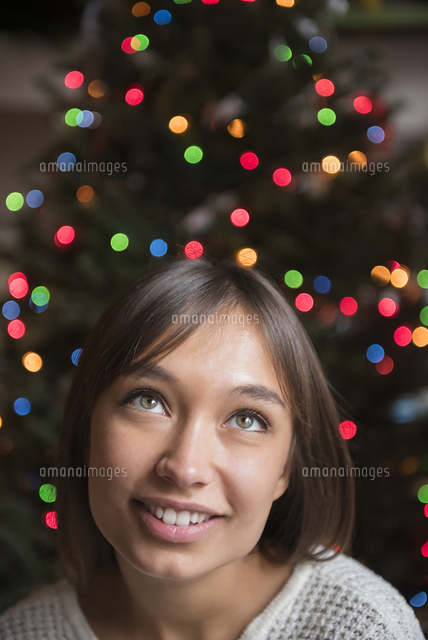 Pensive Mixed Race woman near Christmas tree