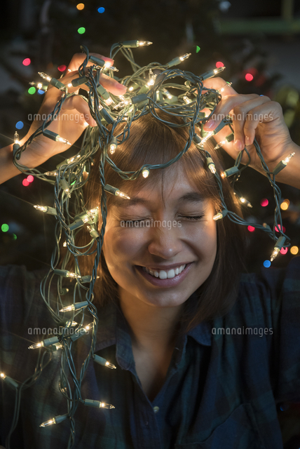 Mixed Race woman holding string lights on head near Christmas tree