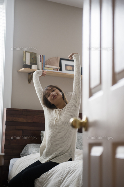 Mixed Race woman stretching arms on bed