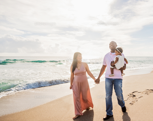 Couple walking on beach with baby daughter