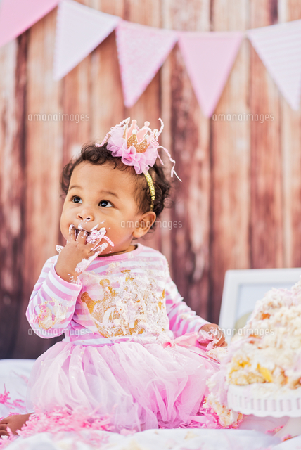 Mixed Race baby eating birthday cake