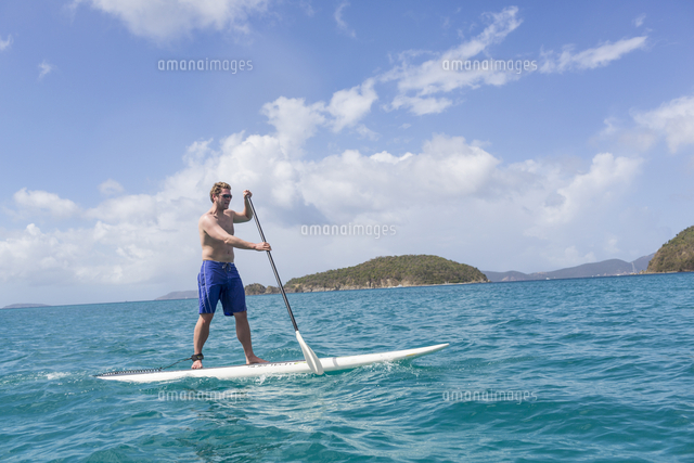 Caucasian man standing on paddle board on ocean