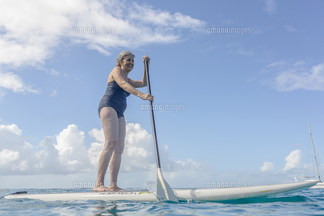 Caucasian woman standing on paddle board on ocean