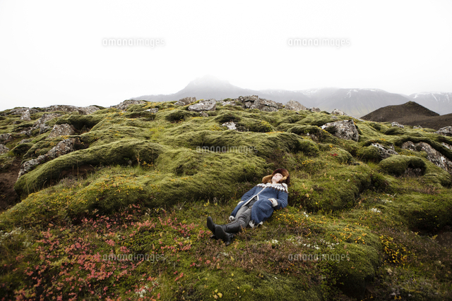 Caucasian woman laying on mossy rocks