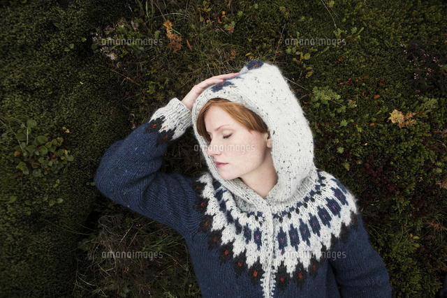Caucasian woman wearing sweater laying on moss