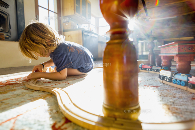 Caucasian boy playing with toy race track on floor