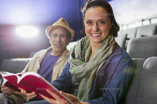 Portrait of Caucasian actors sitting in audience with scripts in theater