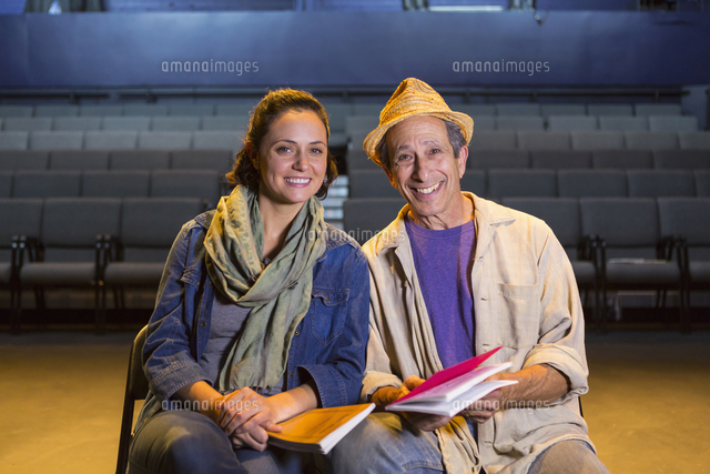 Portrait of Caucasian actors with scripts in theater