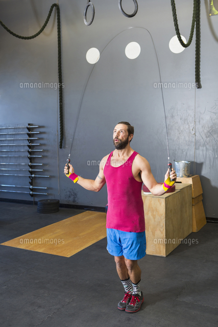 Mixed Race man jumping rope in gymnasium