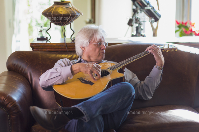 Caucasian man playing guitar on sofa