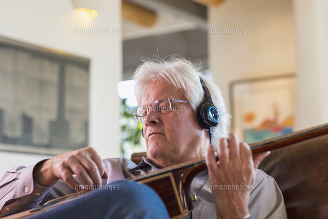 Caucasian man listening to headphones and playing guitar
