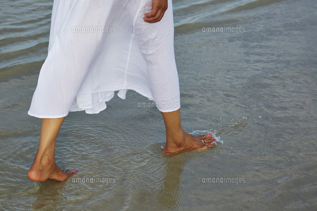 Woman wading barefoot in ocean
