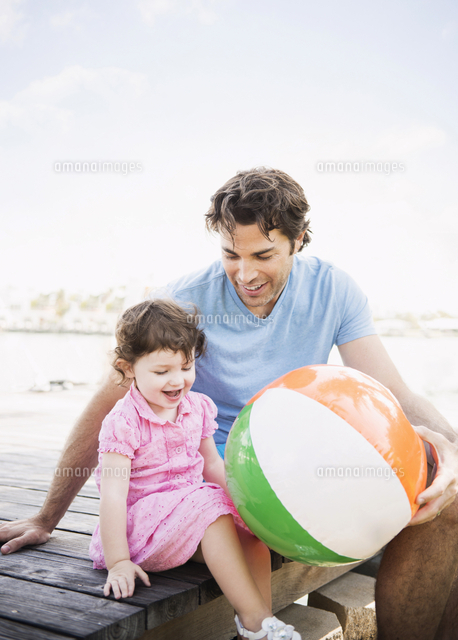 Caucasian father and baby daughter sitting on dock with beach ball