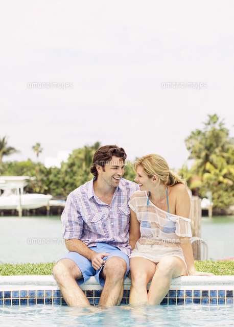 Caucasian couple sitting at the edge of swimming pool