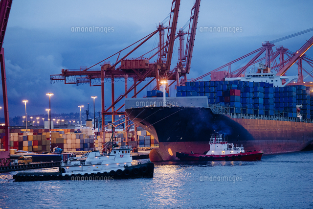 Cargo containers on freighter at shipping port near tugboats