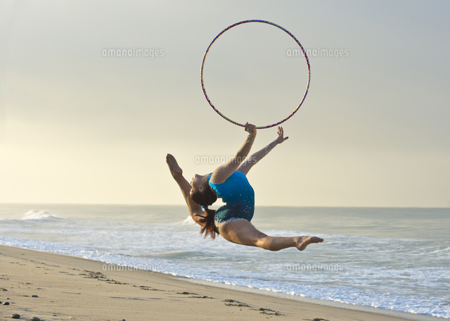 Caucasian gymnast jumping with hoop on beach