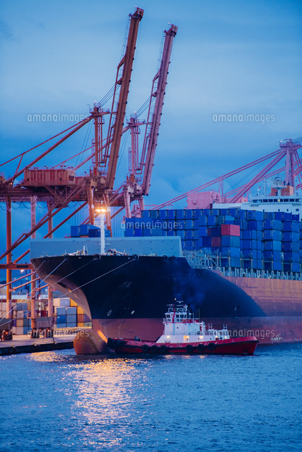 Cargo containers on freighter at shipping port near tugboat