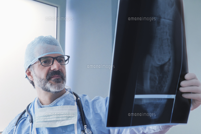 Hispanic surgeon examining x-ray