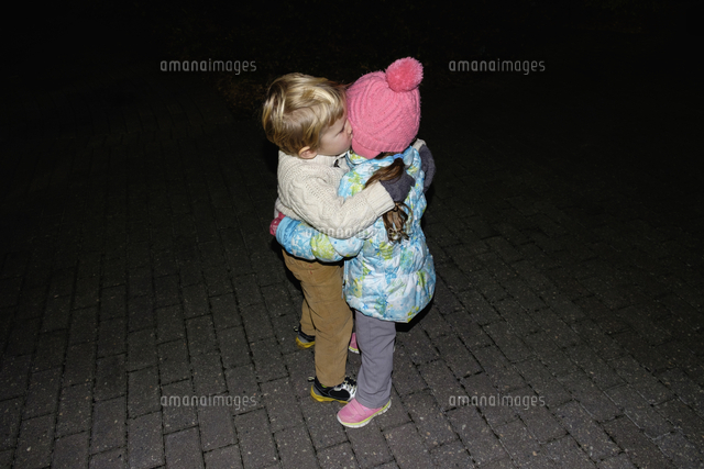 Boy ad girl hugging outdoors at night