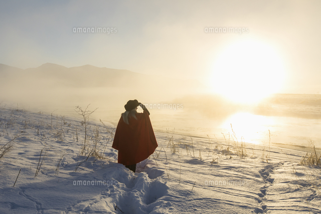Caucasian woman shielding eyes in winter landscape at sunset
