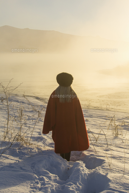Caucasian woman standing in winter landscape at sunset