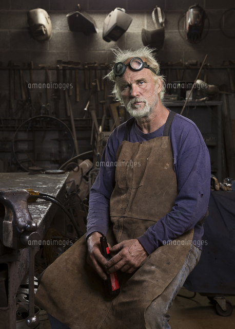 Portrait of serious Caucasian blacksmith in workshop drinking beer