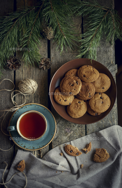 Cookies and tea on wooden table with pine cones