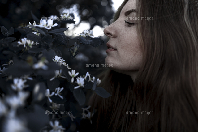 Caucasian woman smelling flowers outdoors