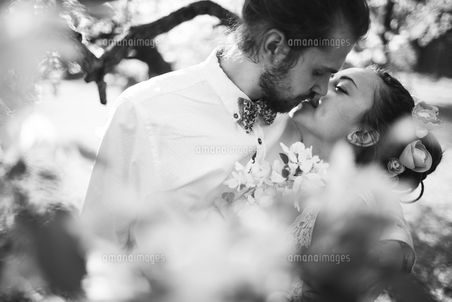Middle Eastern couple kissing near flowers